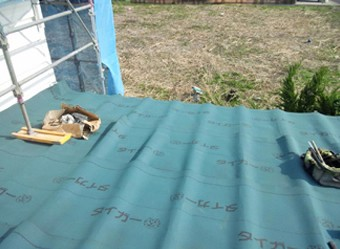 屋根に防水紙を設置している様子